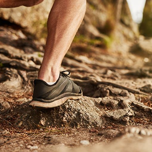 Closeup of man trail running on rocky terrain
